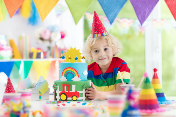 bright colored toddler birthday party with toddler boy wearing birthday hat